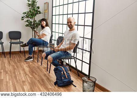 Two hispanic person smiling happy using smartphone at waiting room.