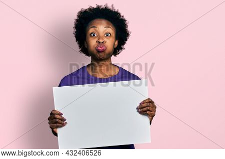 African american woman with afro hair holding blank empty banner puffing cheeks with funny face. mouth inflated with air, catching air.