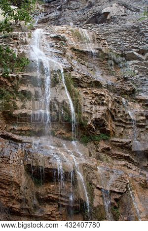 Parched Waterfall In The Mountains. Drying Waterfall Flows From The Cliff