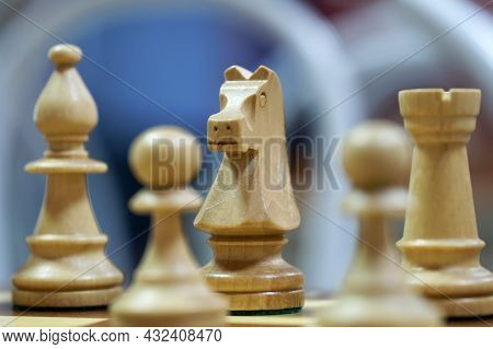 The Knight And Other Chess Pieces Are Standing On The Chessboard. Heterogeneous Blue Background. Mac