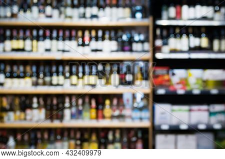 Abstract Blur Wine Bottles On Liquor Alcohol Shelves In Supermarket Or Wine Store Background