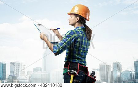 Young Building Controller With Clipboard Standing And Filling Examination Report. Side View Of Woman