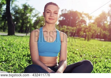 Beautiful Smiling Girl In Sportswear Relax In Park. Portrait Of Young Charming Woman Sitting On Gree
