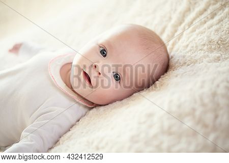 A Charming Baby In A White Sunny Bedroom. A Newborn Baby Is Resting In Bed. Children's Room For Smal