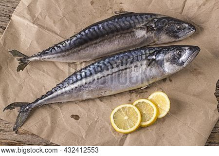 Two Freshly Frozen Mackerels On Wrapping Paper With Lemon Wedges.