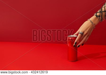 Womans Hand With Spooky Nail Design Takes Can On Red Background In Sunlight