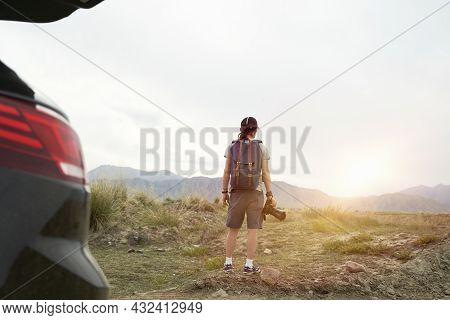Rear View Of An Asian Photographer Traveling By Car Looking At View In The Morning Sunlight With Cam