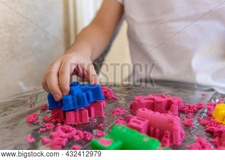 Closeup Of Childs Hands Playing In Kinetic Sand. Selective Focus Shot Of Kids Hands With Red Kinetic
