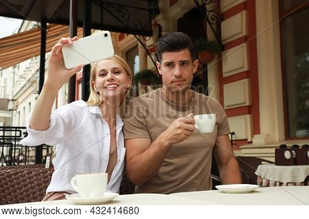 Young Woman Trying To Take Selfie With Her Displeased Boyfriend In Outdoor Cafe. Boring Date