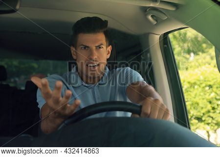 Stressed Angry Man In Driver's Seat Of Modern Car, View Through Windshield