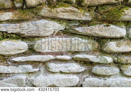 Close Up And Soft Focus Of An Old Wall With A Masonry Of Stones Overgrown With Moss