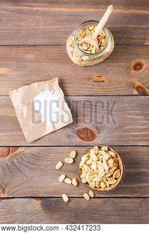 Salted Peanuts In A Bowl And In A Jar With A Spoon And Salt On Paper On A Wooden Table. Healthy Vege