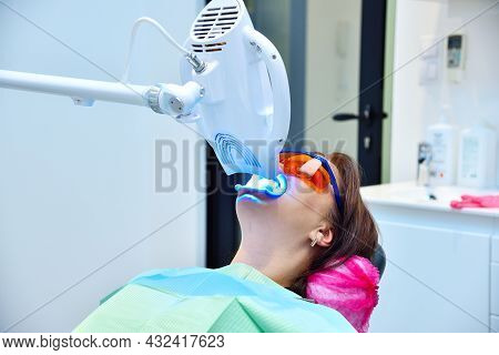 Teeth Whitening Procedure With Ultraviolet Light Lamp. Dental And Teeth Whitening Concept.