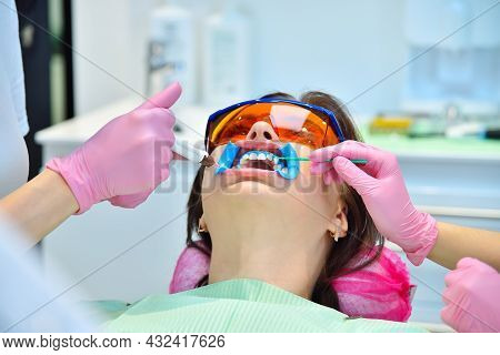 Teeth Whitening For Woman In Dentist Clinic. Dental And Teeth Whitening Concept.