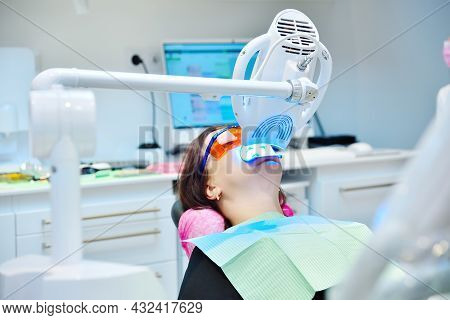 Female Patient In Clinic. Teeth Whitening Procedure With Ultraviolet Light Lamp. Dental And Teeth Wh