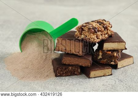 Different Energy Bars And Protein Powder On Grey Table, Closeup
