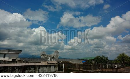 Cumulus Clouds In The Blue Sky At Noon From A Building Roof