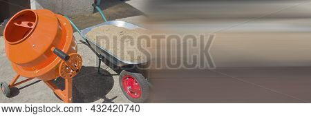 Cement Mixer Machine At Construction Site With Wheelbarrow, Tools, Sand And Cement Bag. Orange Concr