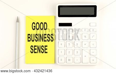 Text Good Business Sense On The Yellow Sticker, Next To Pen And Calculator