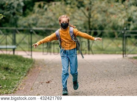 Preteen school girl with backpack wearing face mask running in the park after lessons. Carefree child kid at autumn outdoors in pandemic time