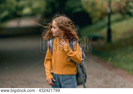 Beautiful girl child with back pack after school looking back at the street at autumn. Portrait of preteen female kid outdoors