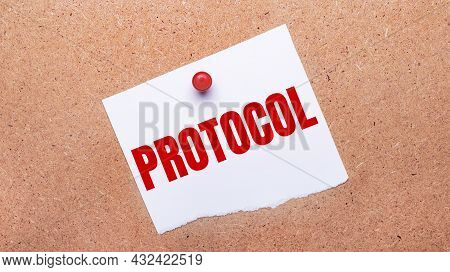 White Paper With The Text Protocol Is Attached To The Wooden Background With A Red Button.
