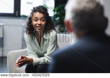 Amazed African American Journalist Sitting In Armchair And Smiling Near Blurred Guest