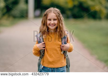Beautiful girl child with back pack after school smiling and looking at camera. Portrait of preteen female kid outdoors at autumn