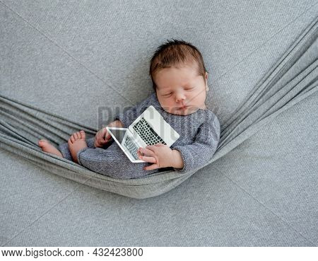 Newborn baby boy wearing in knitted costume sleeping in hammock and holding toy laptop. Infant kid studio portrait with decoration
