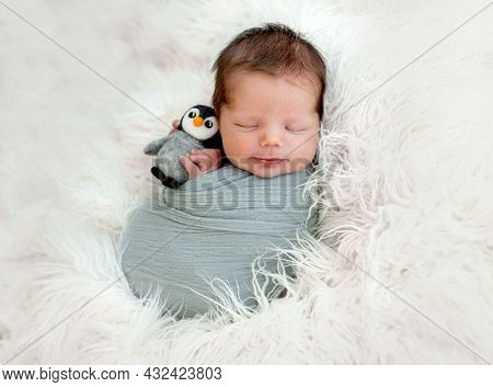 Newborn baby boy sleeping swaddled in fabric on white fur and holding knitted toy in tiny hands. Infant kid studio portrait with decoration