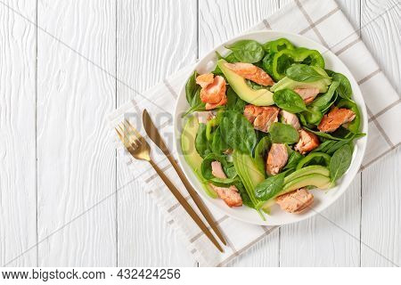 Salmon Spinach Avocado And Green Pepper Salad On A White Plate With Golden Fork And Knife On A White