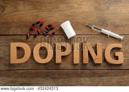 Word Doping And Drugs On Wooden Background, Flat Lay