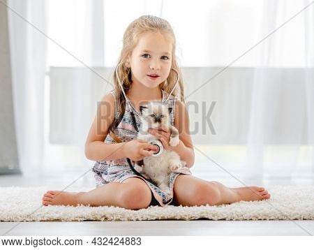 Little child girl playing veterinarian doctor with ragdoll kitten indoors. Pretty female kid hearing heart of feline domestic kitty pet and looking at camera