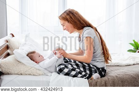 Beautiful young mother holding legs of her adorable little baby boy in her hands and looking at the child. Pretty girl with kid in the bed in morning time. Happy family moments