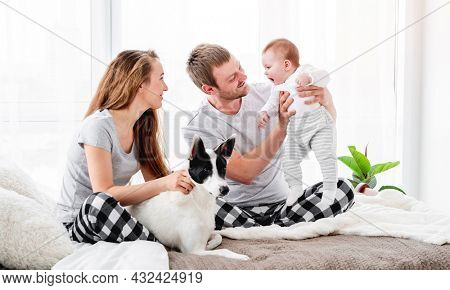 Happy family with baby boy sitting on the bed with cute dog. Mother and father with their son and doggy together in room with daylight. Beautiful parenthood time. Pet with owners