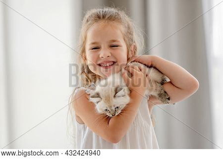 Lovely child girl holding ragdoll kitten and smiling at camera. Pretty female kid happy with feline domestic kitty pet at home