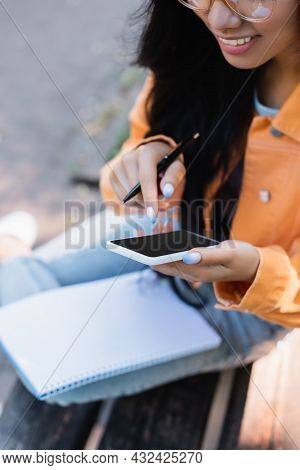 Partial View Of Smiling Woman Using Mobile Phone With Blank Screen Outdoors