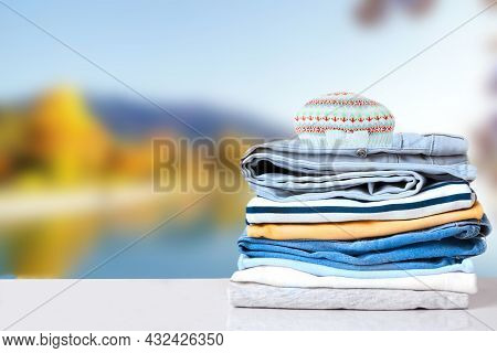 Stack Of Jeans. Closeup Of Stack Of Colorful Denim Pants And Colorful Sweaters And A Cap On A Bright