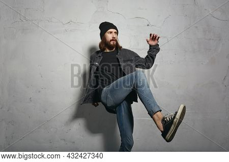 Young focused european man up leg like hitting ball. Stylish guy wearing cap, sweater and jeans jacket. Isolated on white wall background. Studio shoot. Copy space
