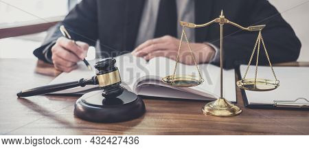 Male Lawyer Or Judge Working With Contract Papers, Law Book And Wooden Gavel On Table In Courtroom,