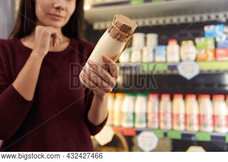 Young european woman watching information about milk product in food store. Concept of shopping. Partial view of beautiful brunette girl. Idea of healthy eating