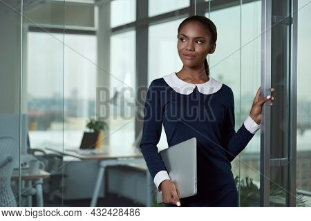 Focused african businesswoman standing and holding laptop computer in modern office. Concept of successful woman. Young black girl wearing formal clothes. Daytime
