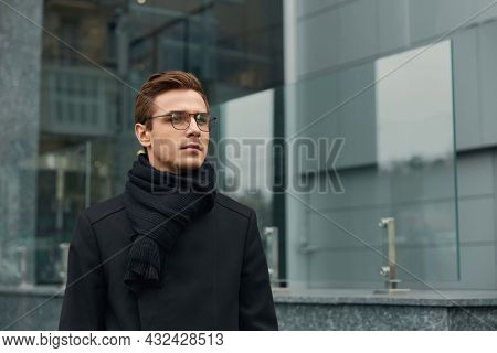 Young serious european businessman standing in modern city. Concept of modern successful man. Handsome stylish guy wearing scarf, coat and glasses. Daytime