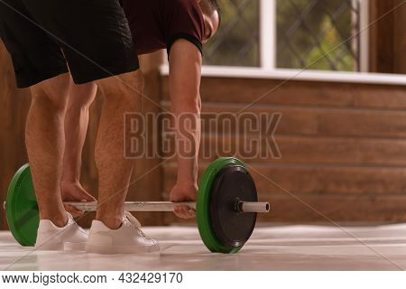 Young Sports Man Bent Gripping A Weight Set Equipment For Weight Training At Home. Sports Equipment