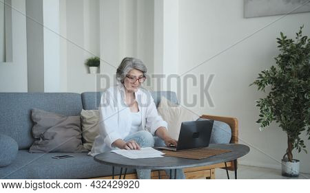 Elderly Businesswoman With A Focused Expression Holds A Fiscal Paper With Commercial Information