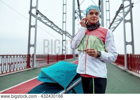 Sportive Woman Wearing Earbuds While Standing On The Bridge With A Baby Carriage, Ready For Morning