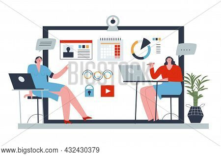 Two Girls Sitting At Desks With Laptops And Discussing Working Points. In The Background Is A Laptop