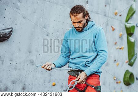 Young Man Professional Rock Climber Checking Sports Equipment Before Climbing At Training Center In
