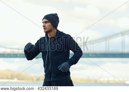 European runner running at cold weather. Young sportsman wearing hat, hooded zipper sweatshirt and mittens. Man prepare to sport run competition. Person listen music in earphones. Urban area. Daytime