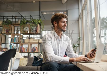 Young smiling european businessman using laptop computer and looking from window. Concept of modern successful man. Bearded stylish guy wearing formal clothes. Office interior. Daytime